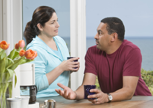 Man and woman talking over coffee at kitchen counter.