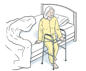 Woman sitting at edge of bed with walker.