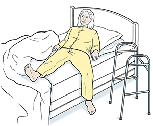 Woman lying down in bed. Walker by bed.
