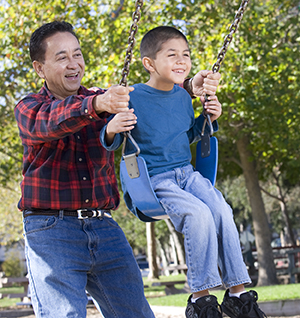 Man pushing boy on swing in park.