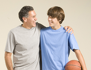 Father with arm around teen son's shoulder, with basketball