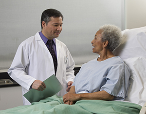 Woman wearing a hospital gown in hospital bed talking with healthcare provider.