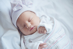 A newborn baby sleeping, wrapped in a blanket.