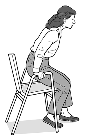 Woman holding armrests of chair and keeping back straight as she sits down.