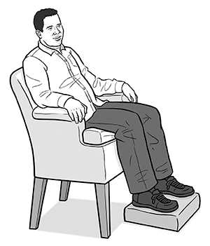 Man sitting in chair with back straight and feet on footrest.