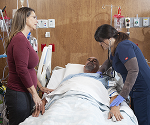 Healthcare provider caring for man in intensive care unit bed while woman stands nearby.