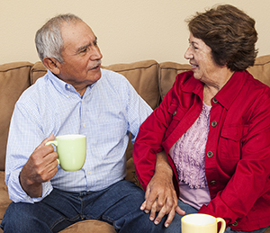 Older man and woman sitting on couch, talking.
